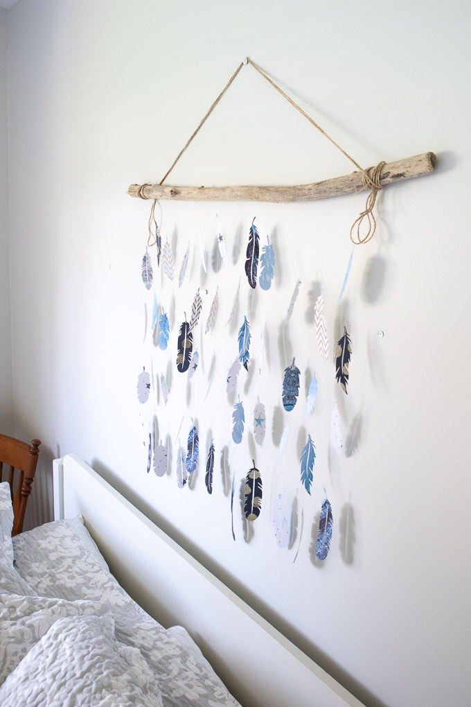 Wall decor made with blue, white and patterned paper feathers hanging from a piece of driftwood by a fishing line.