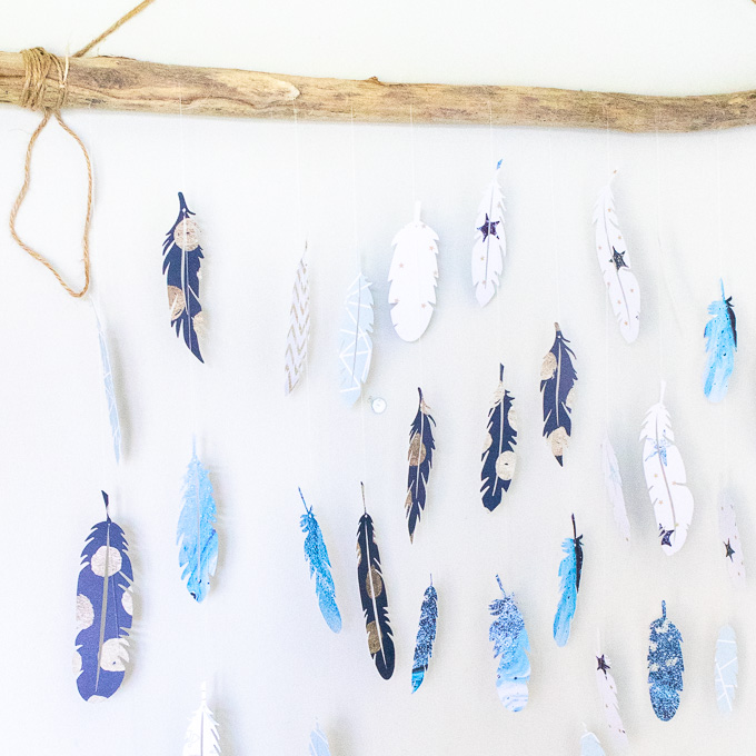 Finished wall decor paper feathers hanging from a long piece of driftwood.