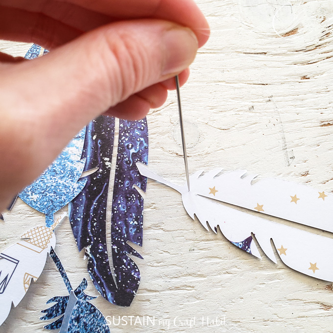 Using a sewing needle to poke a hole through a paper feather.