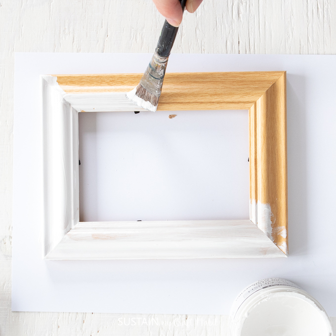 Painting a wood picture frame with white paint.