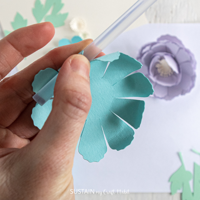 Using a straw to curl the ends of the cut out blue flower.