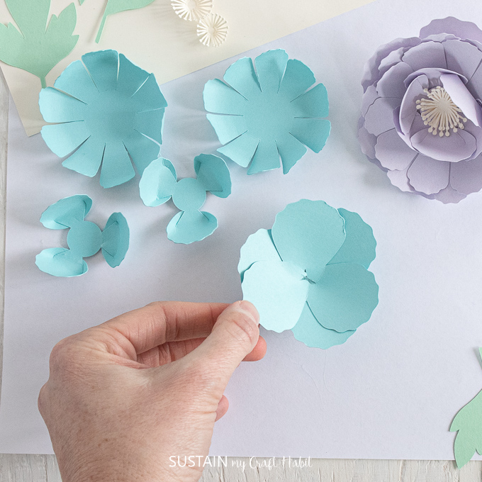 Gluing a blue petal to the top of another petal.