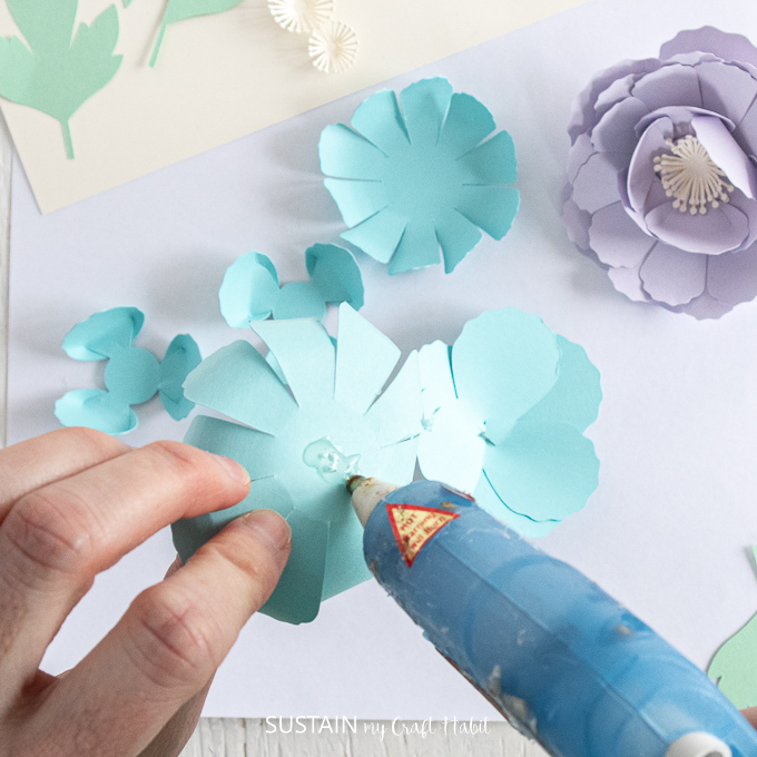 Adding hot glue to the bottom of the blue petal.