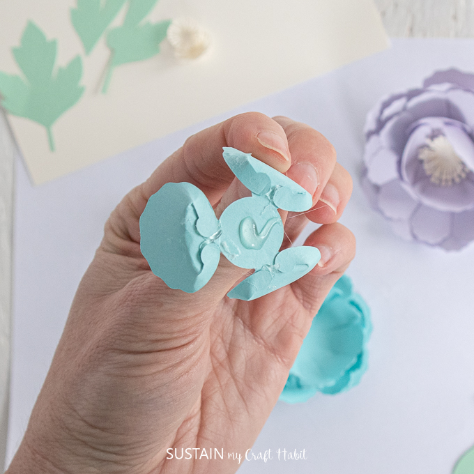 Adding glue to the back of the small blue flower petal.