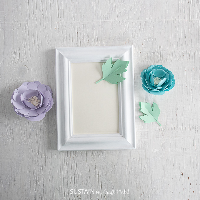Blue and purple peonies, a white picture frame and two green leaves.