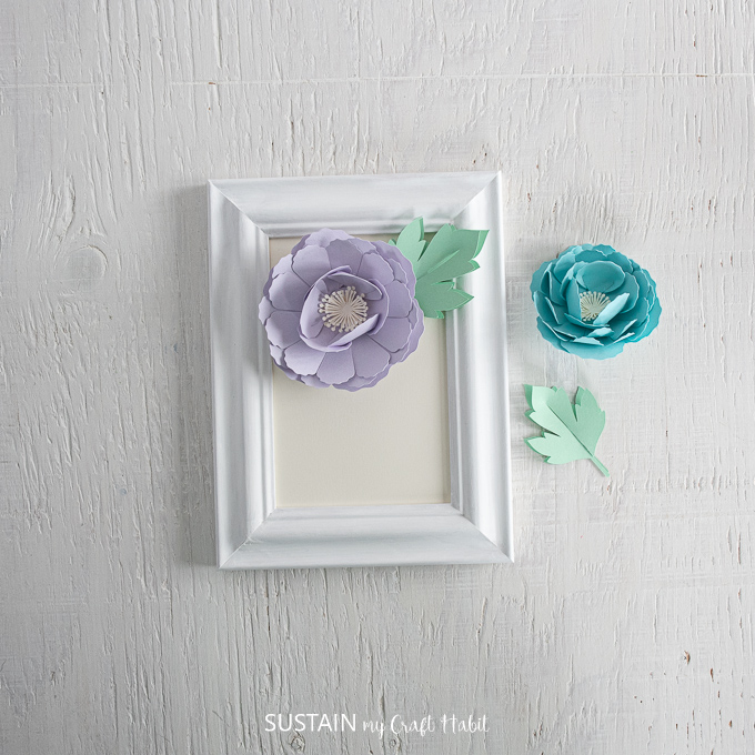 Arranging the purple peony and green leaf onto the white picture frame.