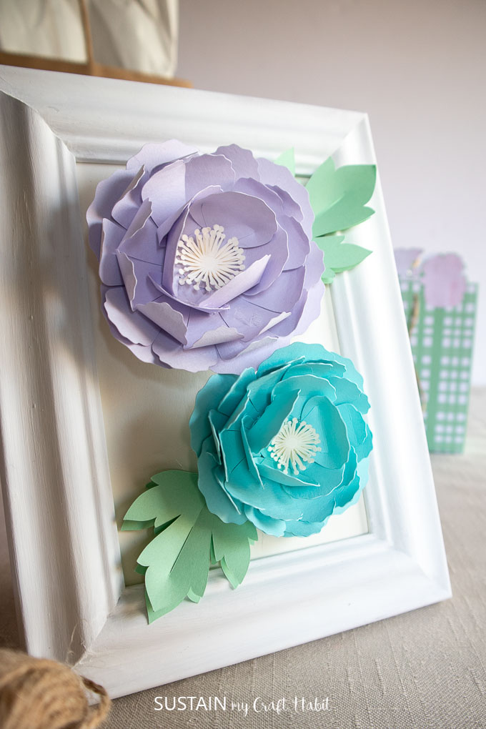 Close up of blue and purple 3D peony flowers placed in a white picture frame.