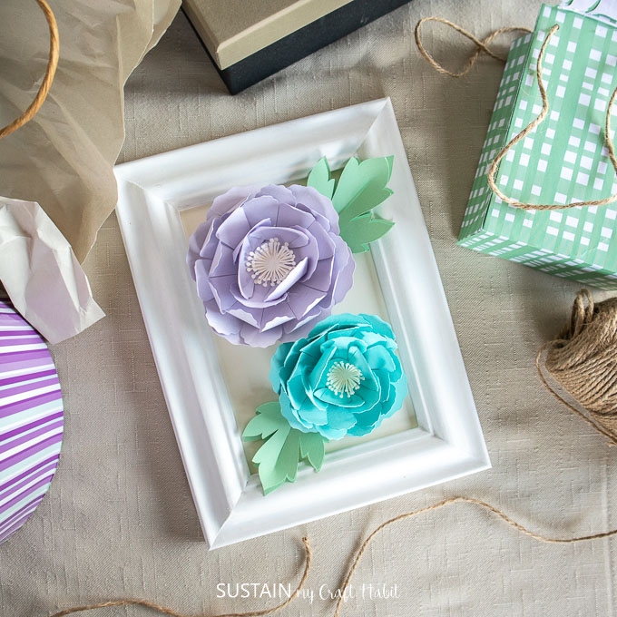 Blue and purple 3D peony flowers placed in a white picture frame.