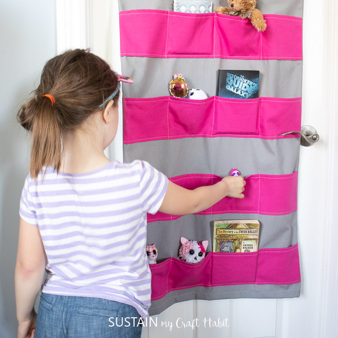 girl using the hanging toy storage to sort her toys
