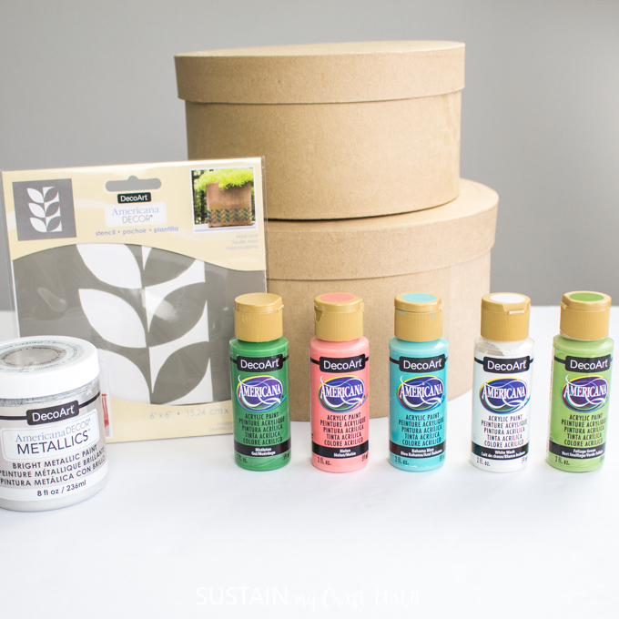 Materials needed to paint the modern retro craft hat boxes, including two hat boxes, paints, and a leaf stencil.