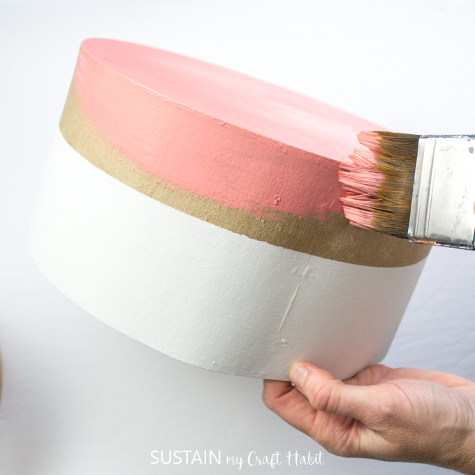 Painting the lower half of a craft hat box with pink paint.