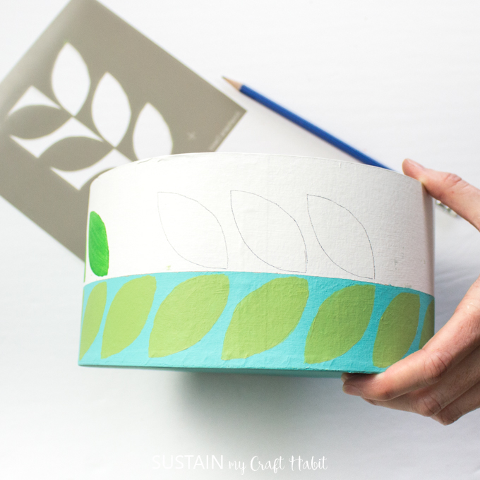 Showing the traced leaf pattern from the stencil on the craft hat box.