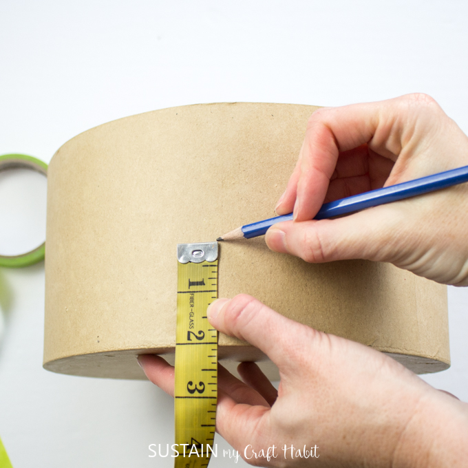 "Using a measuring tape to measure 2"" from the bottom of the craft hat box and using a pencil to mark the spot."