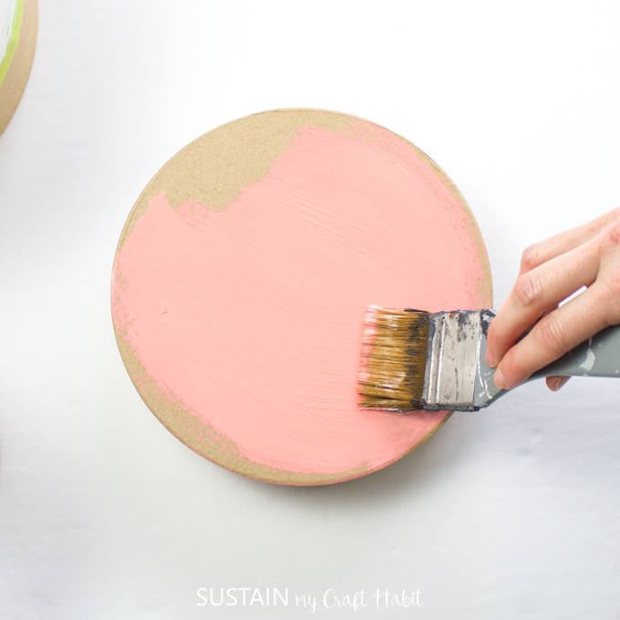 Painting the lid of the craft hat box with pink paint.