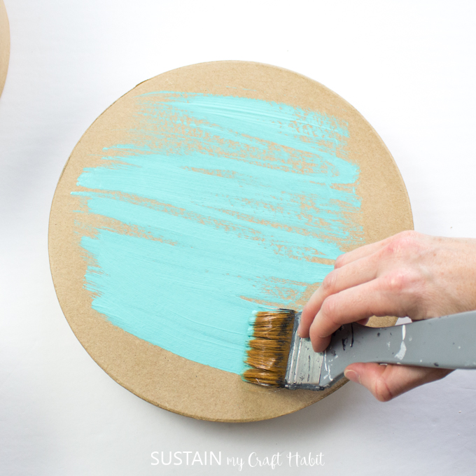 Painting the craft hat box lid with blue paint.