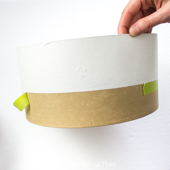 Removing painter's tape from a craft hat box.