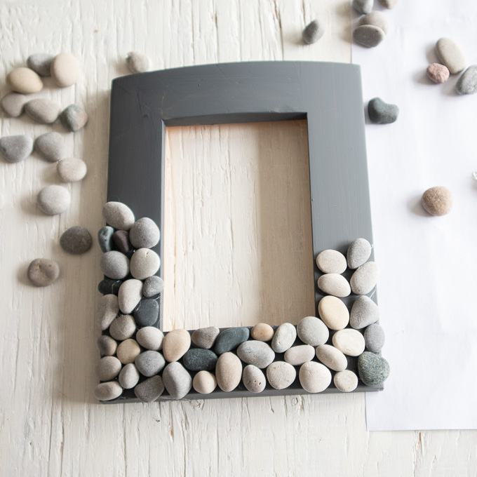 Half of the painted picture frame covered with rocks.