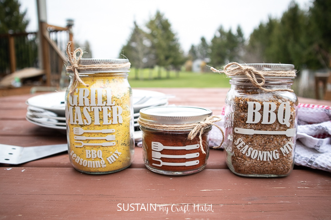 Finished labeled mason jars which are filled with BBQ seasoning and tied with twine, sitting on top of a picnic table as a Father's Day BBQ gift idea