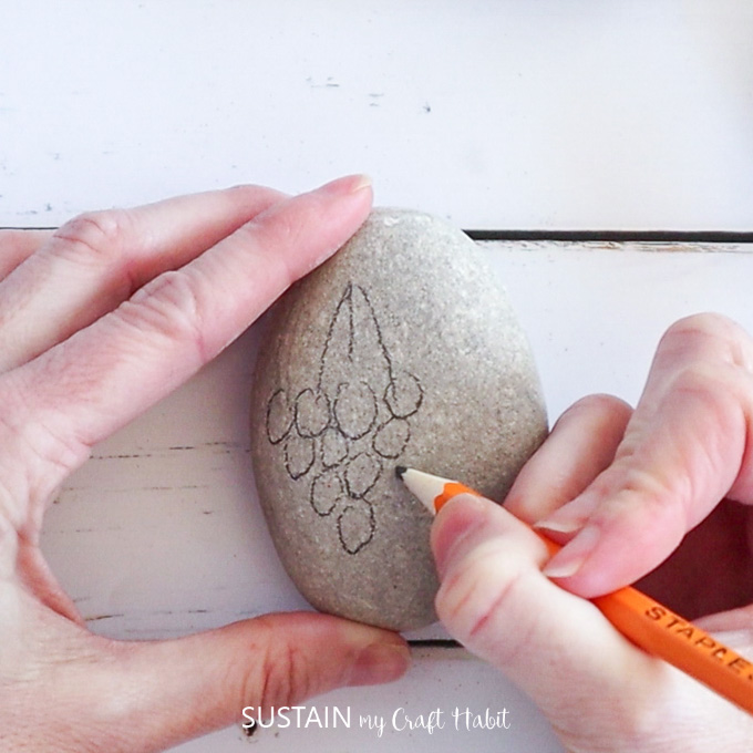 Using pencil to outline shapes of grapes on a rock.