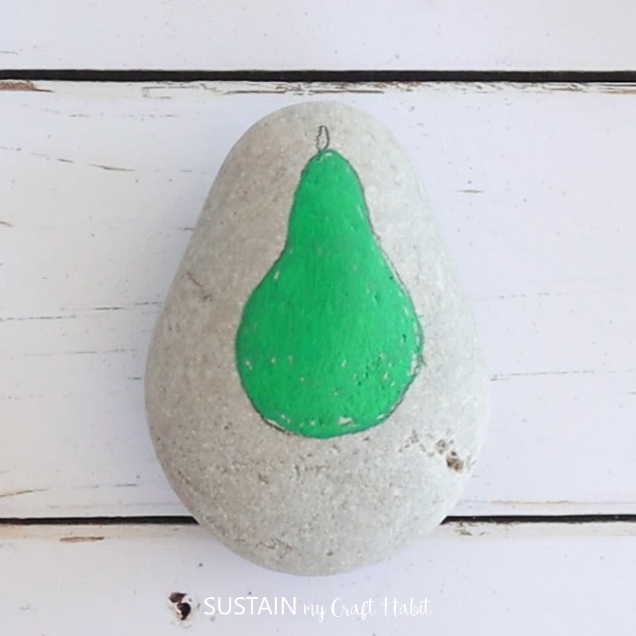 A green painted pear shape on a rock.