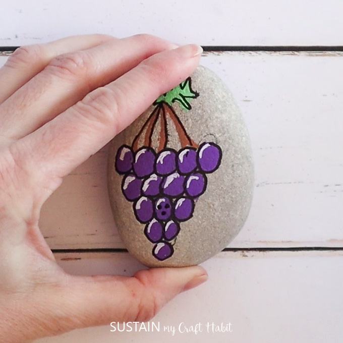 Holding a rock to show the painted grapes and smiley face.