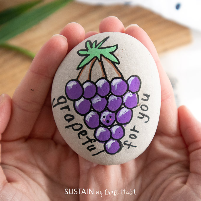 "Holding the finished rock painted with grapes and text ""grapeful for you."""