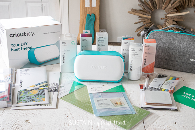 The new Cricut Joy cutting machine along with a variety of accessories and materials arranged on a white wood table.