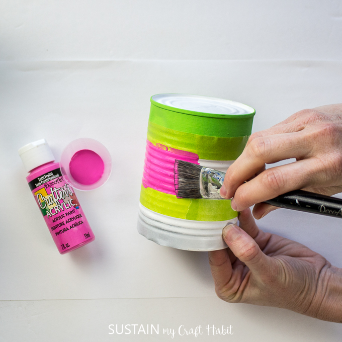Painting the middle of a tin can with pink paint.