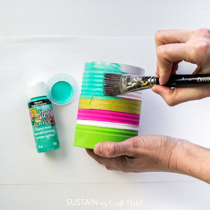 Painting the bottom of the tin can with turquoise paint.
