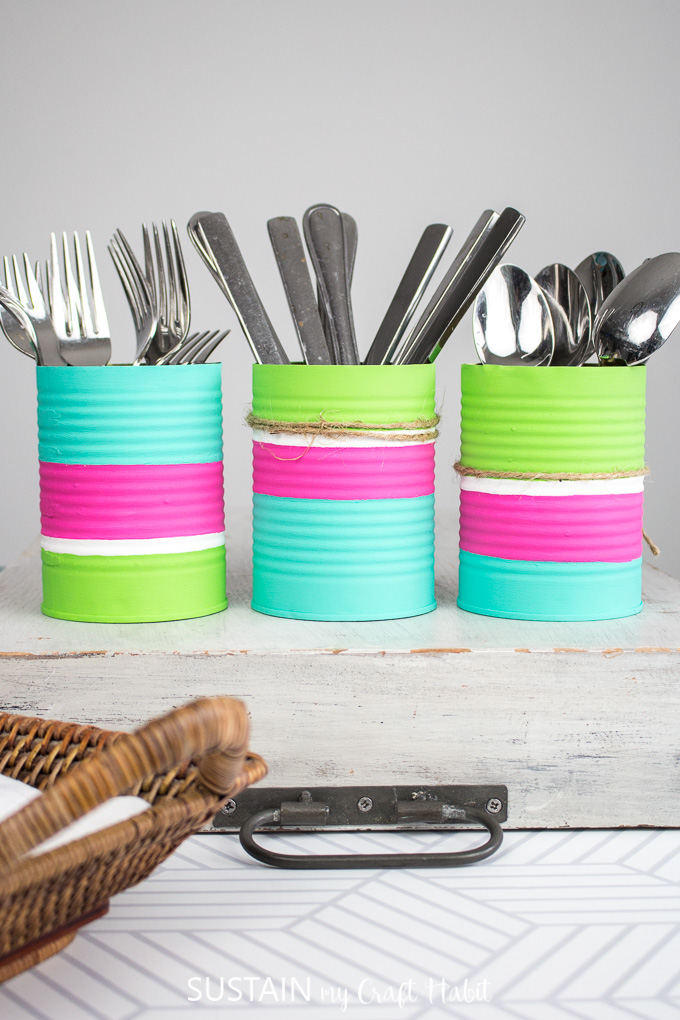 Colorful and painted tin cans upcycled into utensil holders holding forks, knives and spoons.