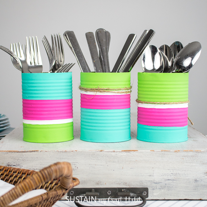 Finished utensil holders with twine wrapped around it and filled with forks, knives and spoons.