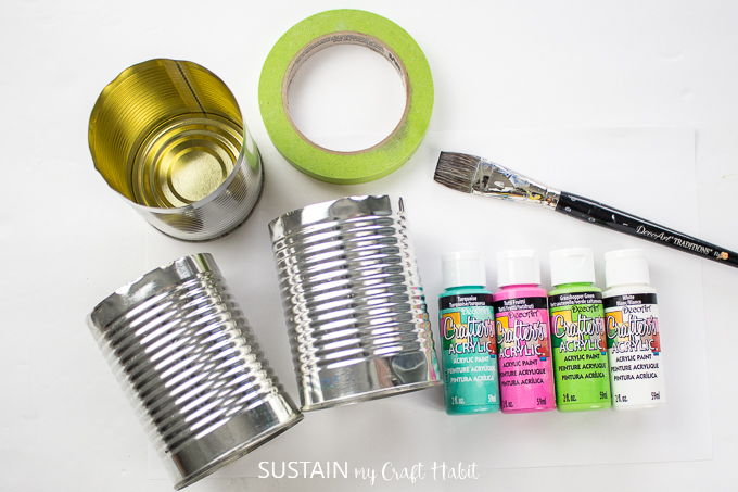 Materials needed to make a colorful utensil holder, including tin cans, paint, tape and a paint brush.