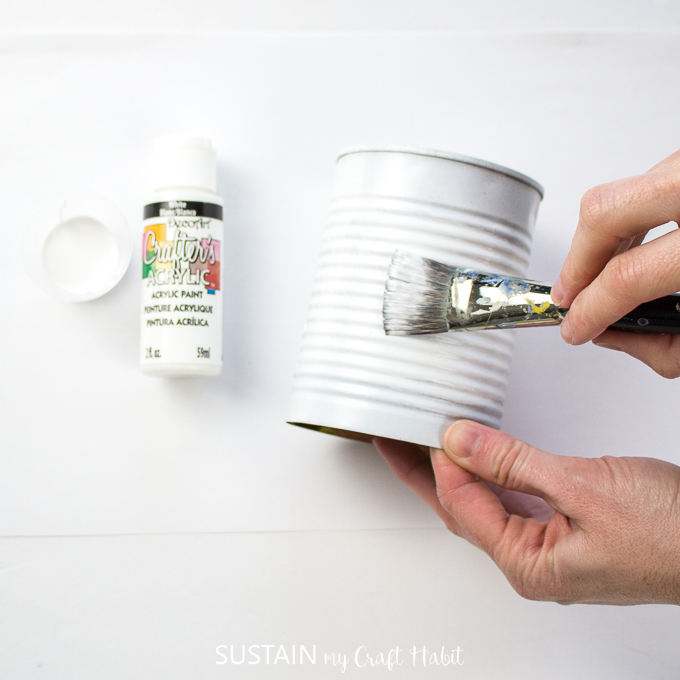 Painting the middle of a tin can with white paint.
