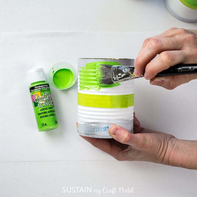 Painting the top of the tin can with green paint.