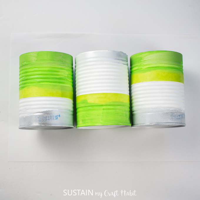 Three tin cans painted in different spots with green paint.