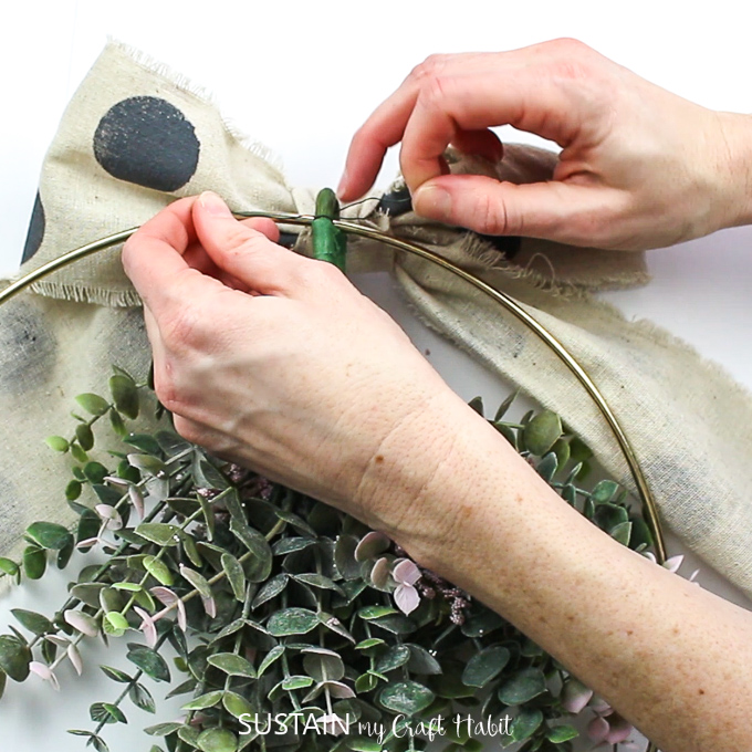 Attaching the canvas bow to the top of the floral hoop wreath.