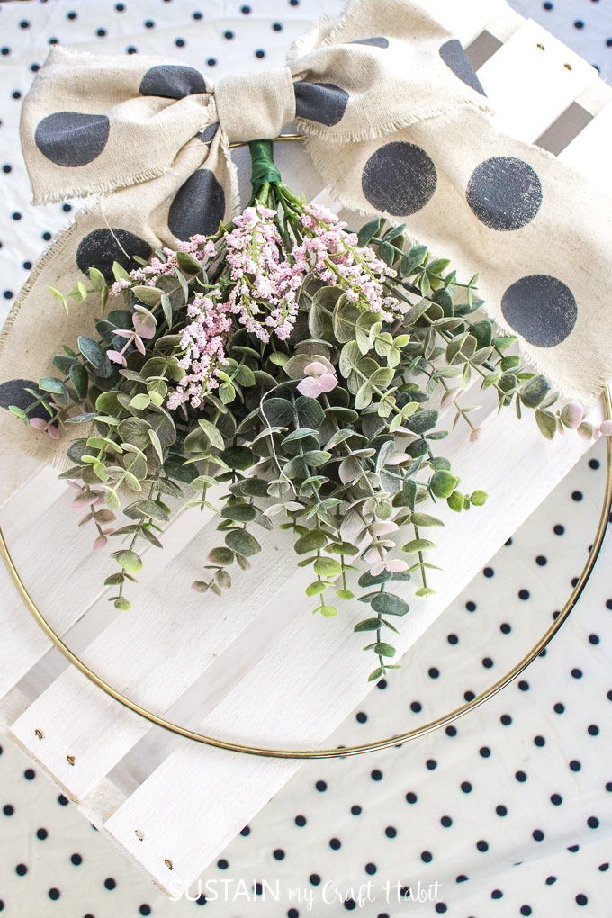 Gold hoop wreath made with eucalyptus plants, pink flowers and a polka dot canvas bow.