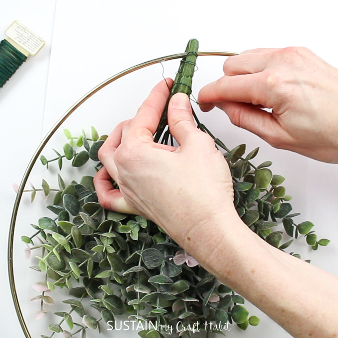 Adding floral wire to the eucalyptus stems to hold them in place.