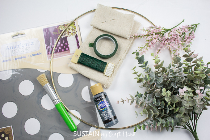 Materials needed to make a floral hoop wreath, including a gold hoop, eucalyptus plants, pink flowers, floral tape, stencil, paint brush, floral tape, paint and canvas.