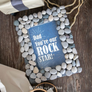 "A picture frame with rocks glued around the frame and text on the glass saying ""Dad you're our rock star!"""