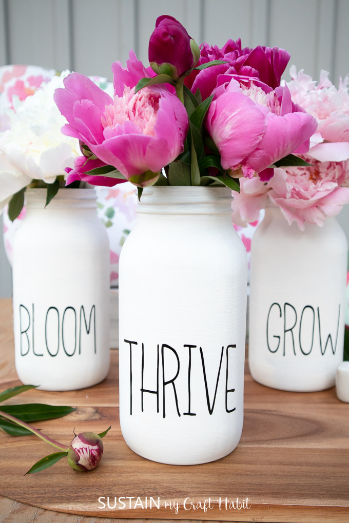 "Finished chalky painted mason jar flower vases with words on the front saying ""bloom,"" ""thrive,"" ""grow"" and filled with peony flowers."