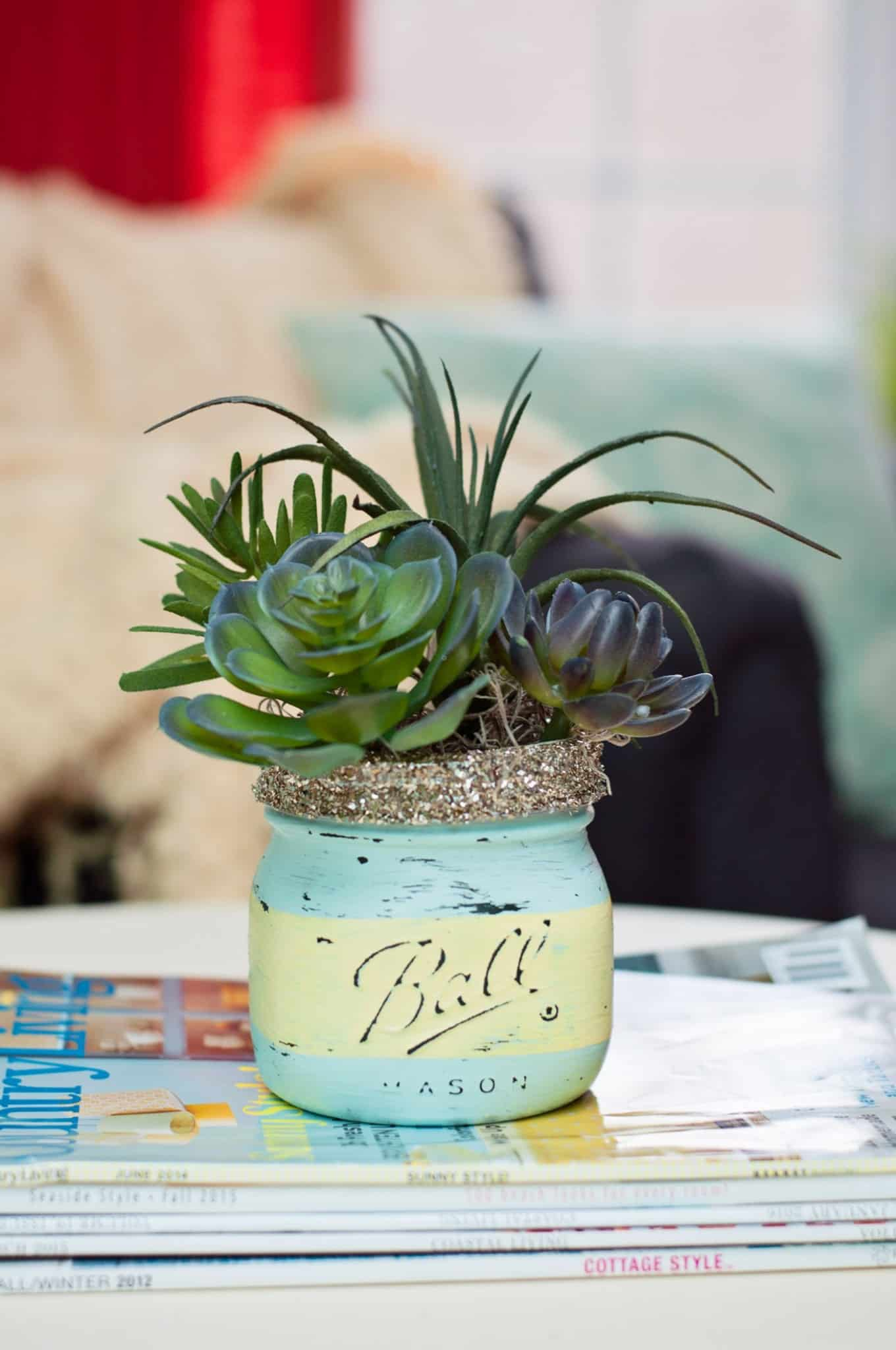 Painted mason jar with a succulent placed inside.