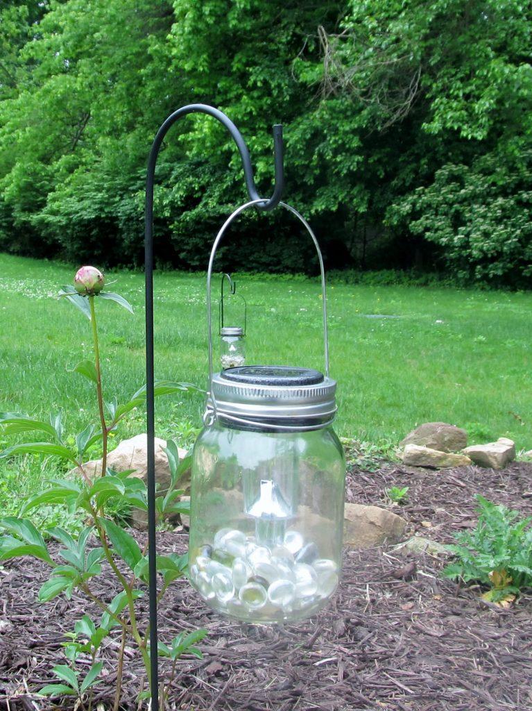 Hanging mason jar solar light in a garden.