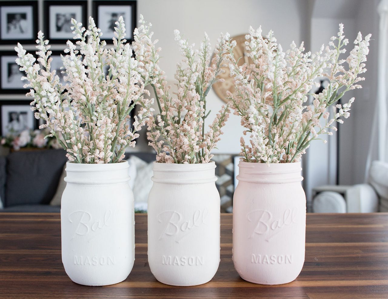 Mason jar vases painted white, cream and light pink with flowers.