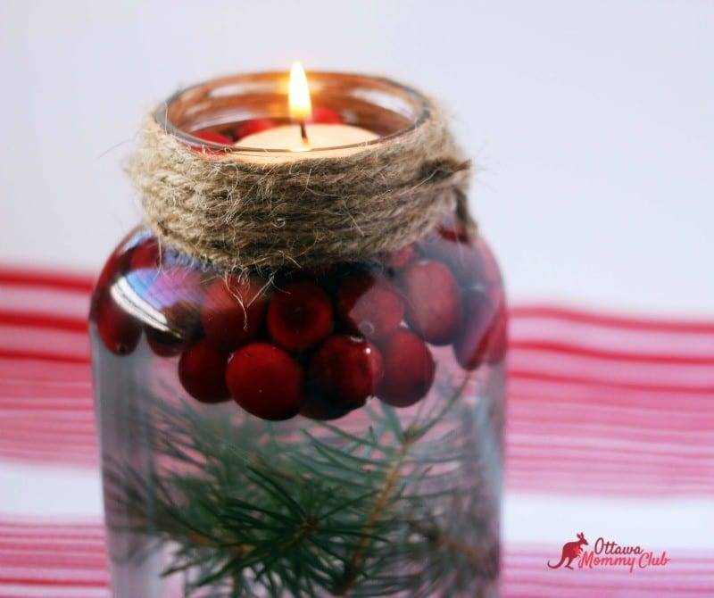 A mason jar candle with tree trimmings and cranberry lit up.