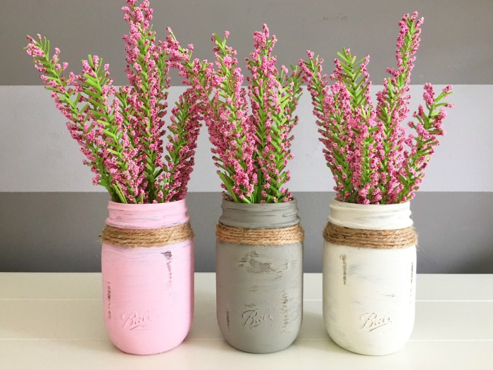 Mason jar crafts painted into pink, great and white flower centerpieces.