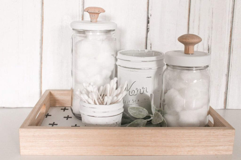Different sized glass jars in a wooden serving tray. Some jars are painted white and other have a lid with a wood knob.