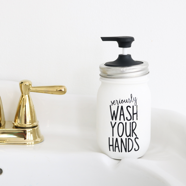 A white painted mason jar with a black soap pump on top. The saying wash your hands is applied to the surface of the jar.