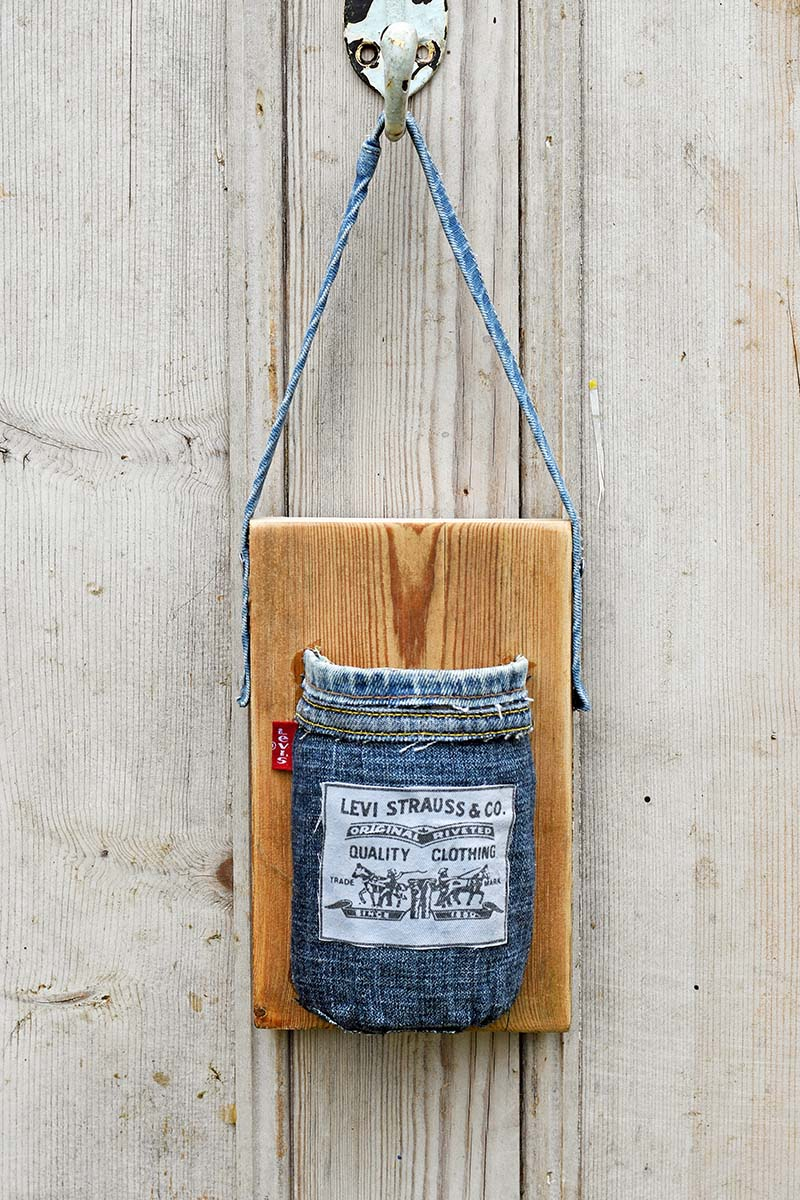 A mason jar wrapped in denim and attached to wood board.