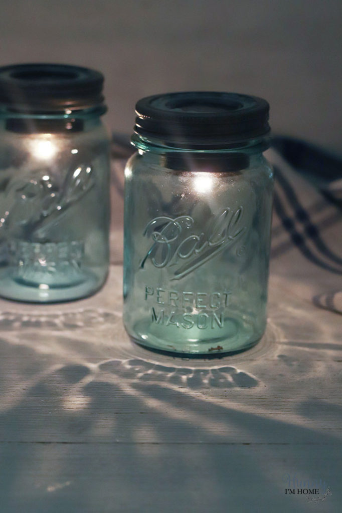 Two mason jar solar lamps lit up.